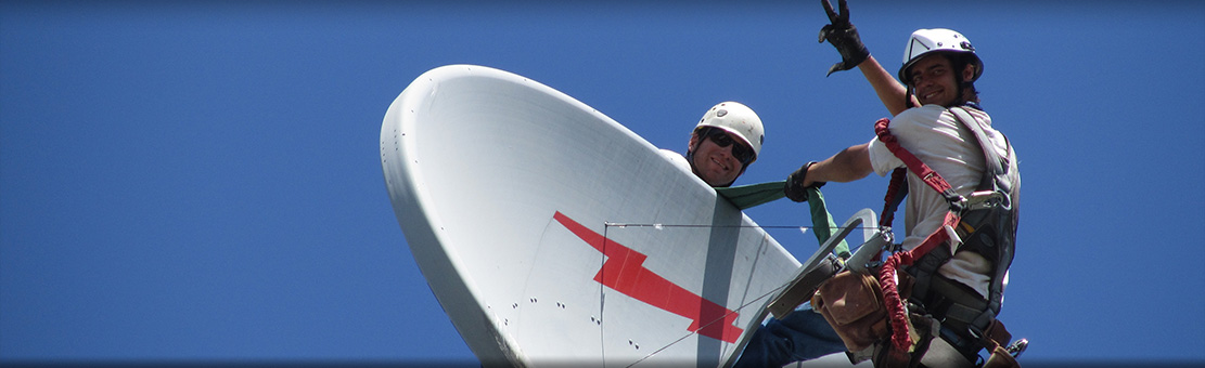 Men connected to safety cables doing some antenna dish checks